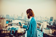 Western businessman using a phone on a rooftop with blurry city royalty free stock photo