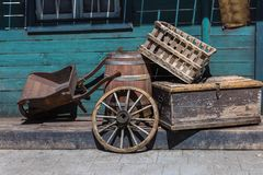 Western Chariot s Wheel, Wooden Wheelbarrow, Cask and Boxes in the Street.  Royalty Free Stock Photography
