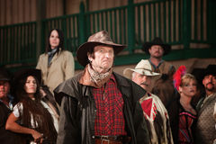 Western Cowboy. Sneering cowboy in trenchcoat with group of people Stock Photography