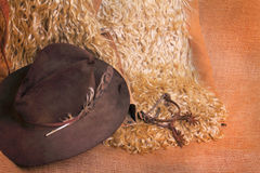 Western Cowboy Gear. Western antique angora woolly cowboy chaps, old worn hat with mangled feather and rusty spurs against burlap. Possible western flyer Royalty Free Stock Image
