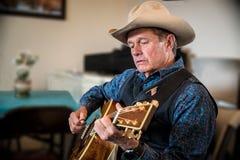 Western cowboy playing guitar. Western cowboy playing western guitar Royalty Free Stock Photography
