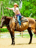 Western cowgirl woman riding horse. Sport activity. Active western cowgirl woman in hat training riding horse. American girl in countryside ranch. Horseback Royalty Free Stock Photo