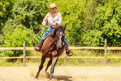 Western cowgirl woman riding horse. Sport activity. Active western cowgirl woman in hat training riding horse. American girl in countryside ranch. Horseback Stock Photography