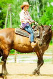 Western cowgirl woman riding horse. Sport activity. Active western cowgirl woman in hat training riding horse. American girl in countryside ranch. Horseback Royalty Free Stock Photography