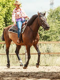 Western cowgirl woman riding horse. Sport activity. Active western cowgirl woman in hat training riding horse. American girl in countryside ranch. Horseback Stock Image