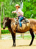 Western cowgirl woman riding horse. Sport activity. Active western cowgirl woman in hat training riding horse. American girl in countryside ranch. Horseback Royalty Free Stock Image