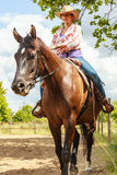 Western cowgirl woman riding horse. Sport activity. Active western cowgirl woman in hat training riding horse. Equestrian sport competition and activity Stock Photography