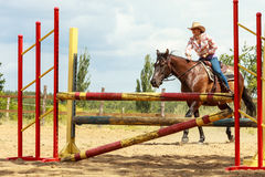 Western cowgirl woman training riding horse. Sport. Active western cowgirl woman training riding horse jumping over fence. Equestrian sport competition and Stock Photo