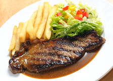Western delights - beek steak. Beef steak served with fries and salad Stock Images