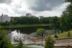 Western Dvina riverfront, Vitebsk, Belarus. Western Dvina riverfront with trees and apertment houses reflecting in the water and overcast sky, Vitebsk, Belarus Royalty Free Stock Photos
