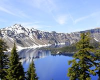 Western edge of Crater Lake and Wizard Island. The west slope of the mountains surrounding Crater Lake and the western edge of Wizard Island in Crater Lake Stock Photos