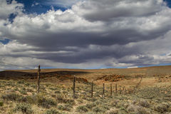 Western Fence Line. Western Cedar Post Fence Across Open Range Land Of The Great Basin Desert With Stormy Cloudy Sky In Background Royalty Free Stock Photo