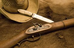 Western Gear. Showing a hat, knife and a old rifle on top of a deer skin stock photos