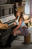 Western girl and piano. Cowgirl with  hat in the western town Royalty Free Stock Images