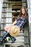 Western girl on the stairs. Cowgirl with  hat in the western town Royalty Free Stock Photo