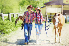 Western happy couple smiling and walking with a horse. Royalty Free Stock Photos