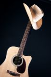 Western Hat On Guitar Neck. A western hat on top an acoustic electric guitar isolated against a low key black background in the vertical format Royalty Free Stock Image