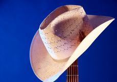 Western Hat On Guitar Neck Blue BK. A western hat on a guitar neck isolated against a blue background in the horizontal format Royalty Free Stock Images