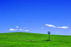 Western Hill with Water Pump Windmill Landscape Royalty Free Stock Photos