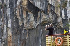 Male Tourist on top deck of tour boat takes photos of rockwall in Ha Long Bay, Vietnam. A Western man is standing on the junk boat`s observation deck taking Stock Photos
