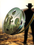 Western movie. A composition representing a film roll with a reflected image  of a western movie at the foreground of that same blur  image Royalty Free Stock Image