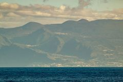 Western part of Tenerife seen from Gomera. Long lens shot. Blue sky with clouds, blue water under straight coast line. Canary royalty free stock image