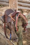Western riding saddle and horse blanket. On wooden corral post after a trail ride Royalty Free Stock Photography