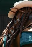 Western saddle with cowboy hat and leather harness. In close-up and the pony stands in the shadow of the trees royalty free stock photos
