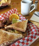 Western Sandwich. Toasted Western sandwich served in a basket with homefries, sliced pickles and an orange slice at the diner stock photography