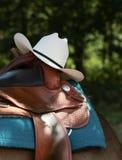 Western-Sattel mit Cowboyhut und Ledergeschirr Lizenzfreies Stockfoto