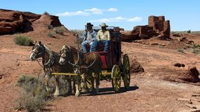 Two cowboys on a stagecoach in the frontier desert scene stock illustration