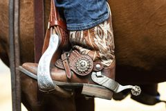 Western spur and stirrup with a lot of bling bling. Western rider`s boot with spur in a stirrup, they ar the boots from a cowgirl stock images