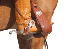 Western stirrup. Rider wearing western boots and spurs with foot in a the stirrup of a western saddle Royalty Free Stock Photography