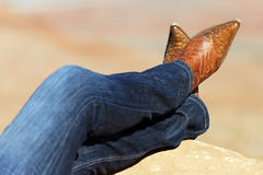 Western style. Image of cowgirl's legs in jeans and boots Royalty Free Stock Image
