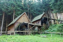 Western style pioneer frontier water mill wheel wooden building in the forest.  Royalty Free Stock Photography