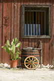 Western style wall, window of hut with barrel, wheel, cactus Stock Photo