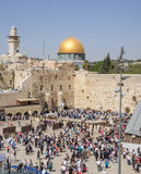 The Western Wall. JERUSALEM, ISRAEL - APRIL 17, 2014: The Western Wall crowded with Passover prayers, and the Dome of the Rock in the background, in the old city Stock Photography