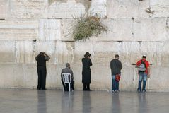Western Wall in the Old City of Jerusalem: Jewish men stand near the stone wall, one old man sits on a white chair, Israel. Stock Photography