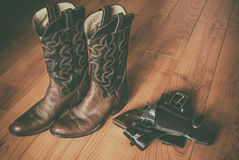 Western Wear Boots and Gun in Holster. Pair of old western cowboy boots and a revolver in a holster sitting on a hardwood floor royalty free stock photo