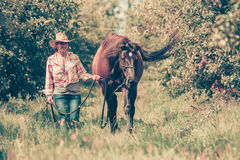 Western woman walking on green meadow with horse Royalty Free Stock Photography