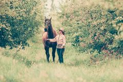Western woman walking on green meadow with horse stock photography