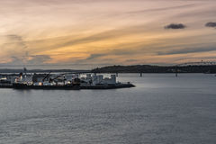 Westhaven oil terminal at sunset in Auckland. Auckland, New Zealand - March 6, 2017: Westhaven oil terminal with docked tanker at sunset. Orange sky, Silver Stock Image