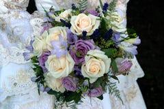 Westhochzeitskleid und purpurroter Hochzeitsblumenstrauß Lizenzfreie Stockfotos