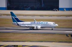 WestJet Boeing die 737 bij de Internationale Luchthaven van Tamper landen Stock Foto