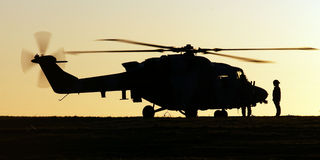 Lynx Helicopter Silouette. A Westland Lynx AH7 helicopter takes on fuel at a temporary refueling point stock photography