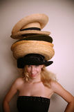 Westliches Mädchen, das viele Hüte trägt Stockbild