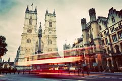 Westminster Abbey church, red bus moving in London UK. Vintage Stock Image