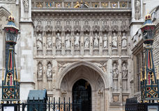 Westminster Abbey London. The entrance of Westminster Abbey with its adorned lamps, several priests statues and an ogival gothic door. London, England stock image