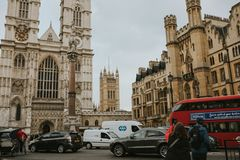 Westminster Abbey and a typical red bus crossing the scene, in London, England. LONDON, ENGLAND - 25th October, 2018: Westminster Abbey and a typical red bus stock photo