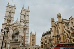 Westminster Abbey and a typical red bus crossing the scene, in London, England. LONDON, ENGLAND - 25th October, 2018: Westminster Abbey and a typical red bus stock images